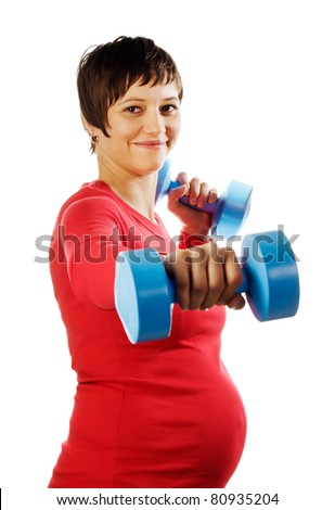 Young pregnant woman in a red shirt making fitness exercises with blue dumbbells. Studio shot against a white background. - stock photo