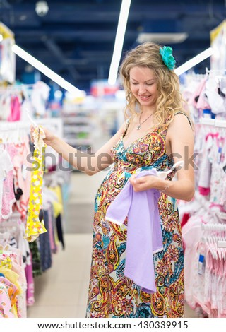 young pregnant woman in baby shop - stock photo