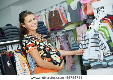 Young pregnant woman in colorful shirt choosing clothes at shopping store - stock photo