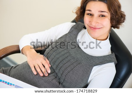 Young pregnant woman in dress working at office - stock photo