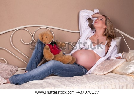 Young pregnant woman in jeans and white shirt  laying in  bed with  teddy bear during pregnancy