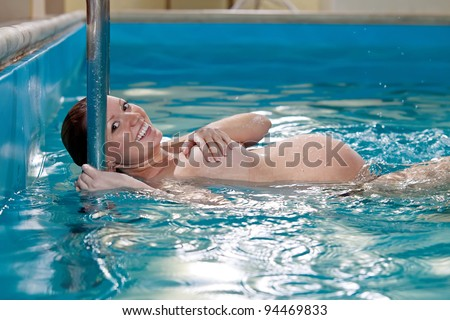 Young pregnant woman in swimming pool - stock photo