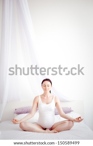 young pregnant woman in the bedroom - stock photo