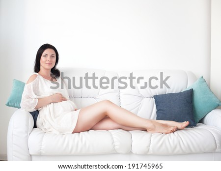 Young pregnant woman in the bright bedroom - stock photo