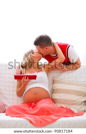 Young pregnant woman kissing her husband who present her jewelery - stock photo
