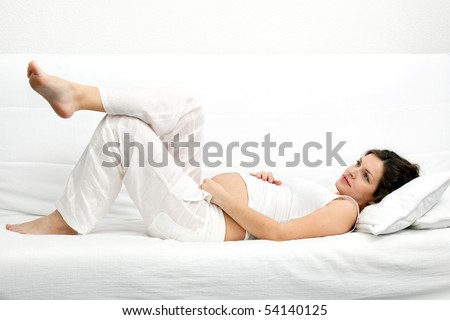 Young pregnant woman laying on sofa