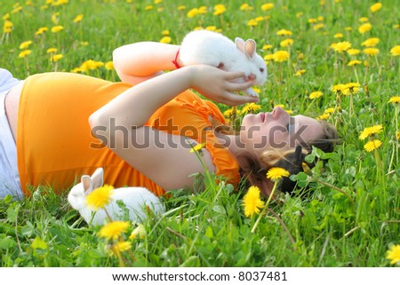 Young pregnant woman lays down on grass and palys with cheerful rabbits - stock photo