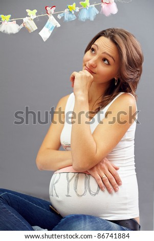 young pregnant woman look at clothesline and think - stock photo