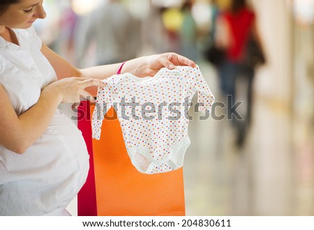 Young pregnant woman looking at new baby clothes in shopping mall - stock photo