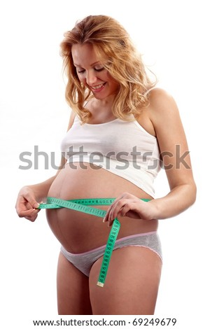 Young pregnant woman measuring her belly and smiling
