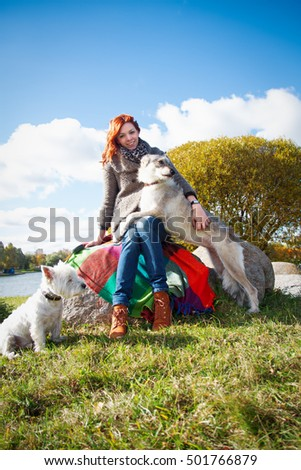 Young pregnant woman playing with dogs in the park in autumn