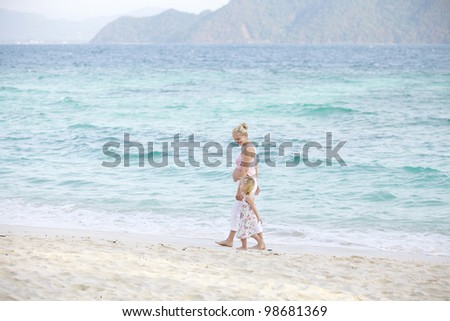 young pregnant woman plays with her daughter on the beach