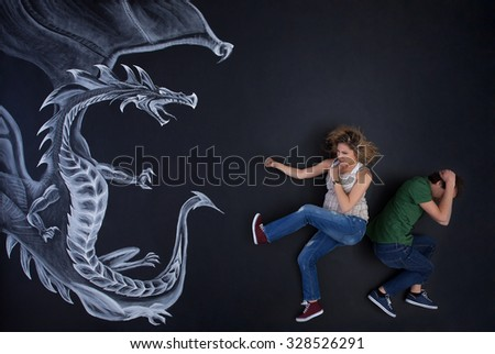 Young pregnant woman protecting his man against a drawing dragon.