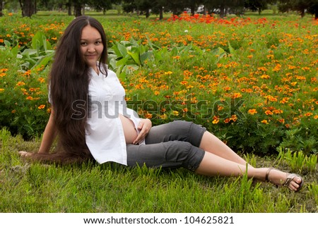 Young pregnant woman relaxing at a park