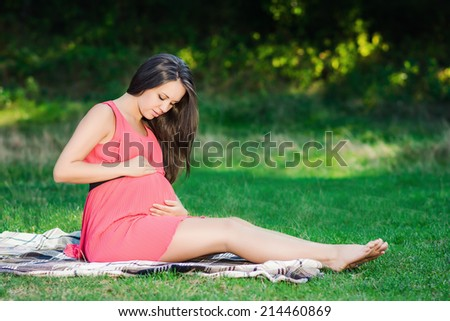 Young pregnant woman relaxing in park outdoors, healthy pregnancy. - stock photo