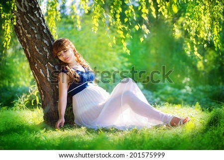Young pregnant woman relaxing in park outdoors, healthy pregnancy. Happy pregnant woman on nature. Beautiful pregnant woman holding her tummy. New life concept.