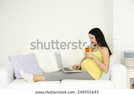 Young pregnant woman relaxing on sofa with laptop on home interior background - stock photo