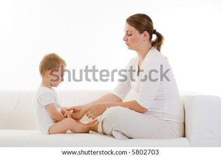 Young pregnant woman sits facing a small child.  Woman is reaching for the child's hand.  Woman is also pregnant.  Both models are in white colored clothing on a white sofa. - stock photo