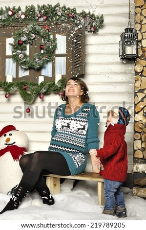 Young pregnant woman sits on a bench with the child about a snowman - stock photo