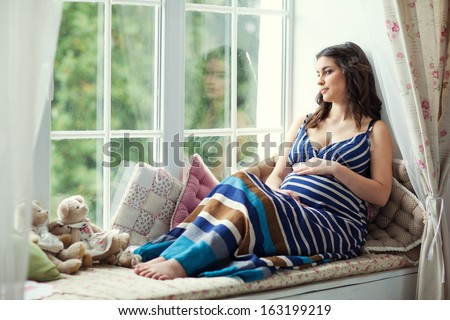 young pregnant woman sitting on the window - stock photo