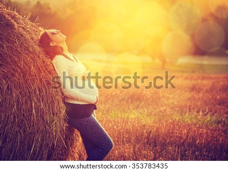 Young Pregnant Woman Standing by the Haystack at Sunset and Embracing her Belly. 7 Month Pregnancy. Happy Maternity Concept. Toned Photo with Bokeh. - stock photo