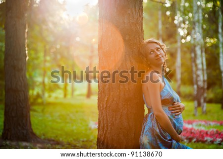 Young pregnant woman standing near tree in summer park and holding belly - stock photo