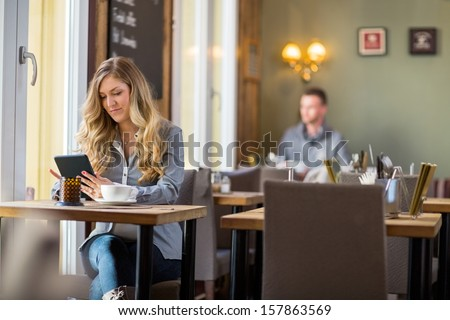 Young pregnant woman using digital tablet at table with man sitting in background - stock photo