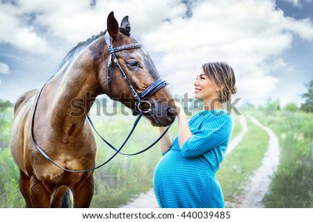 young pregnant woman with a brown horse in the field