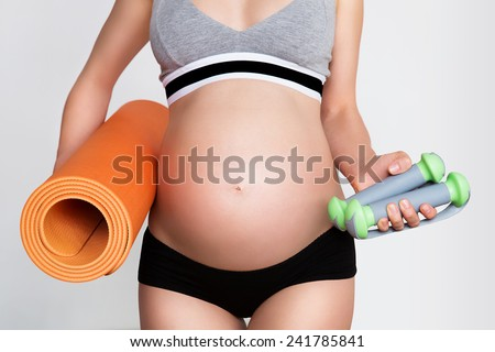 Young pregnant woman with beautiful healthy body holding dumbbells and mat - stock photo