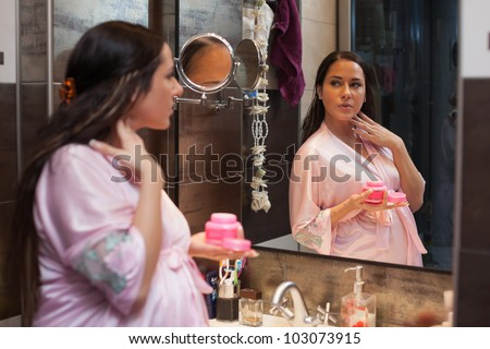 Young pregnant woman with cosmetic cream  in a bathroom. Concept body care. - stock photo