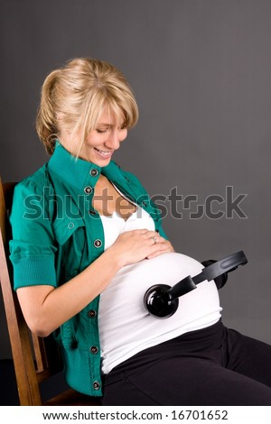 young pregnant woman with headphones on tummy with relaxing music playing for baby in womb