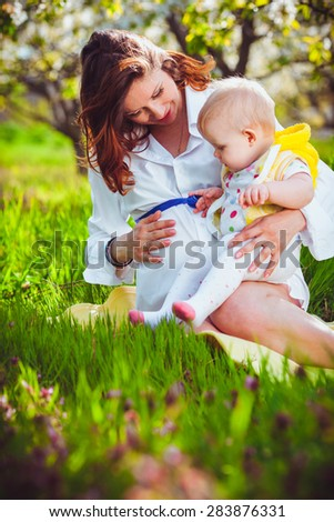 Young pregnant woman with her daughter outdoor - stock photo