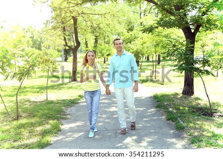 Young pregnant woman with husband walking in park