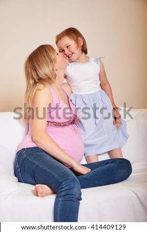 Young pregnant woman with little daughter  - stock photo