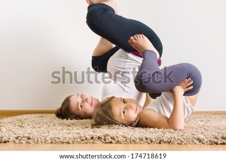 Young pregnant woman with little daughter doing yoga exercises - stock photo