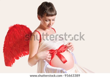 young pregnant woman with red wings - stock photo