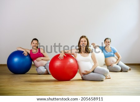 Young pregnant women doing relaxation exercise using a fitness ball - stock photo
