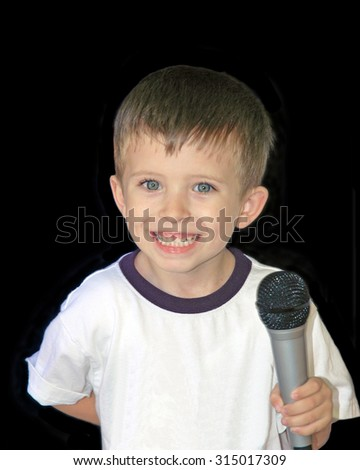young preschool age boy smiling holding a microphone after singing with one hand behind his back - stock photo