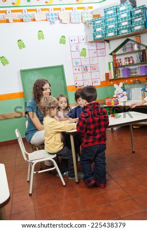Young preschool teacher playing with children in kindergarten - stock photo