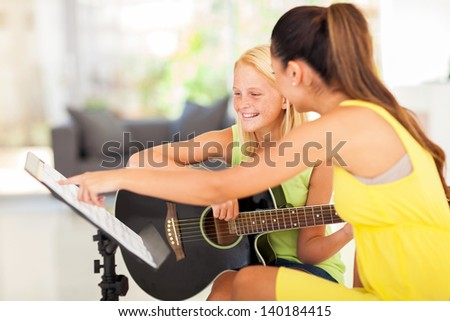 young preteen girl having guitar lesson at home - stock photo