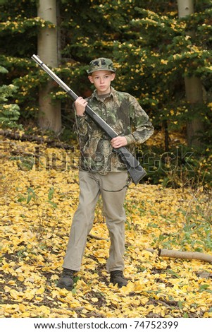 young preteen hunter in deer woods in fall - stock photo