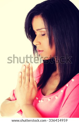 Young pretty adult woman praying. - stock photo