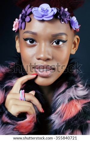young pretty african american woman in spotted fur coat and flowers jewelry on head smiling sweet etnic make up bright - stock photo