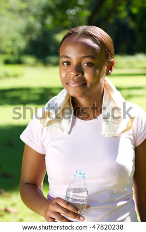 young pretty african american woman jogger drinking water - stock photo