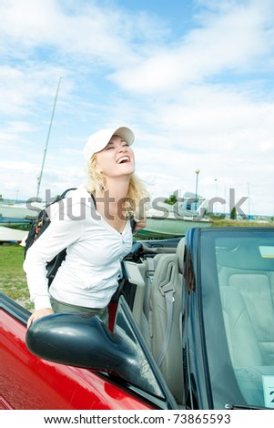 young pretty and beautiful caucasian blond girl with positive facial expression in front of the cabrio car.
