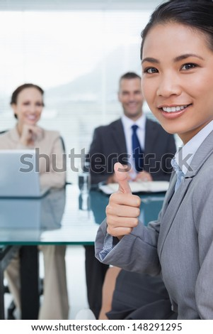 Young pretty applicant in bright office showing thumb up after obtaining the job - stock photo