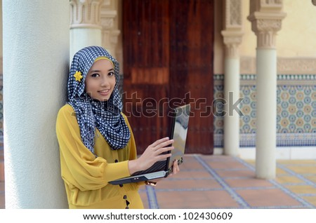 young pretty Asian muslim college girl with laptop and smile