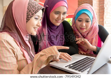 Young pretty Asian muslim college girls having discussion using laptop - stock photo