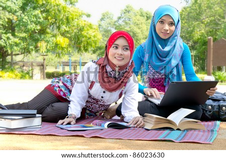 Young pretty Asian muslim college girls having discussion with book and laptop. - stock photo