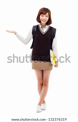 Young pretty Asian student indicate side space, isolated on white background. - stock photo